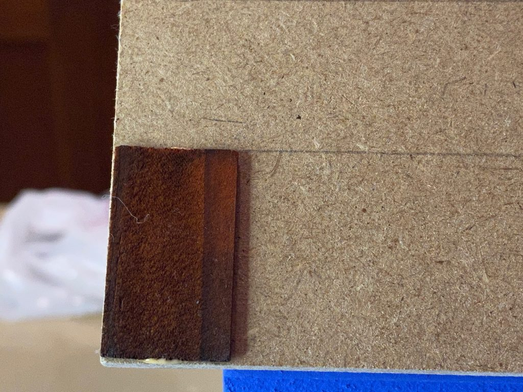 The first shingle on the dollhouse roof