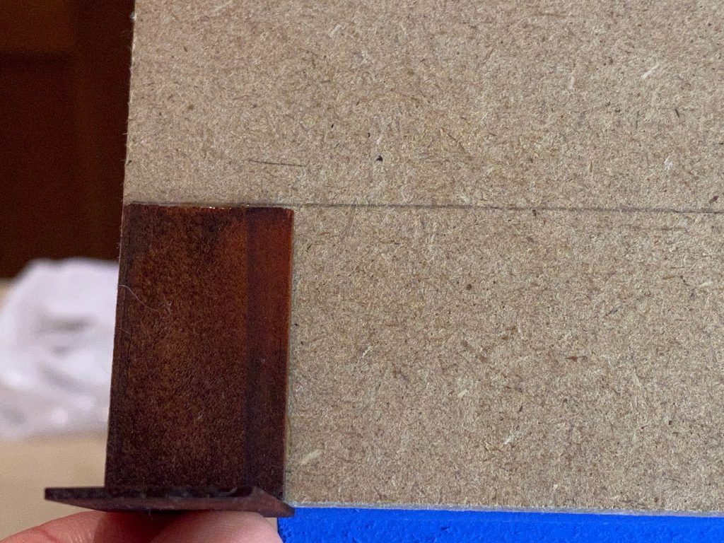 Lining up the dollhouse roof shingles using another shingle as a guide