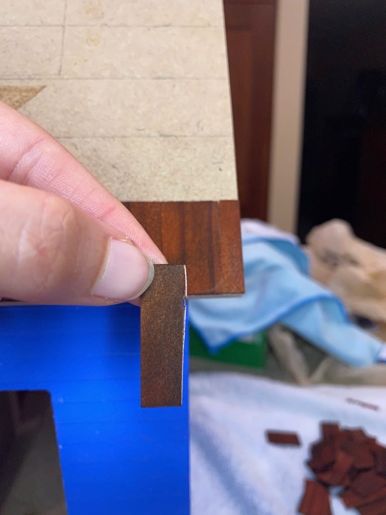 The leftover shingle piece that should fit on the other end of the dollhouse roof